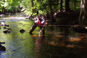 Paul Ferri, Environmental Compliance Analyst, takes measurements of the Fenton River.